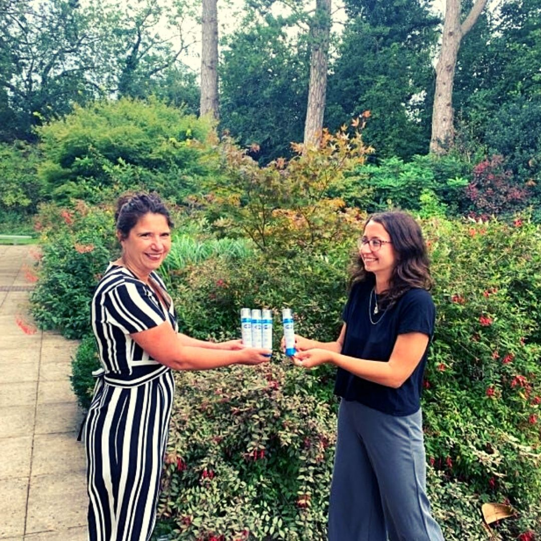 marketing executive from Nilaqua hands over 50 Nilaqua alcohol free sanitiser bottles to the lady from Longfield Hospice In a beautiful garden.